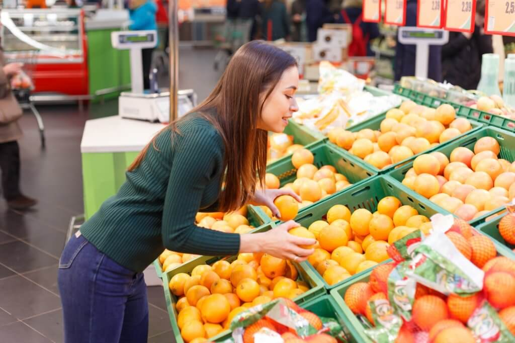 Young girl buys oranges in a grocery store
